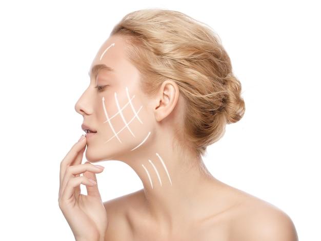 Retrato lateral de uma mulher bonita com pele limpa perfeita com setas no rosto isolado no branco