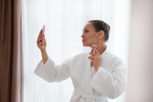 Retrato lateral de uma mulher bonita em roupão de banho massageando o pescoço com um massageador de rolo de pedra de jade e olhando seu reflexo no espelho cuidados com a pele, higiene diária e conceito de spa em casa