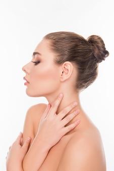 Retrato lateral de uma mulher relaxada e sensível tocando seu pescoço