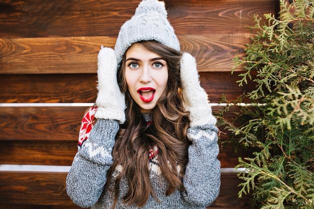 Retrato linda garota com cabelo comprido em roupas de inverno e luvas quentes na madeira. ela parece surpresa.
