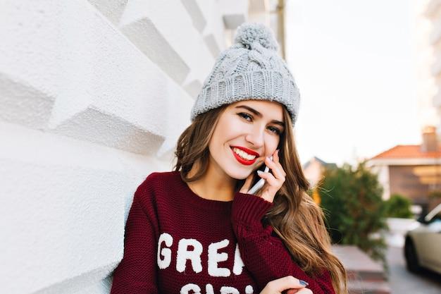 Retrato linda garota com cabelo comprido na camisola de marsala, falando no telefone na rua. ela usa chapéu de malha e sorrindo.