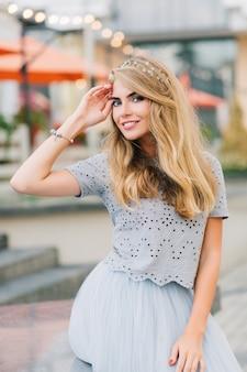 Retrato linda garota com longos cabelos loiros em saia de tule azul, sentada no fundo do terraço. ela mantém a mão na cabeça e sorrindo para a câmera.