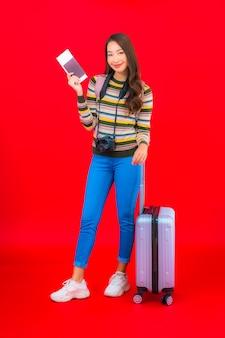 Retrato linda jovem asiática com bagagem e cartão de embarque na parede vermelha