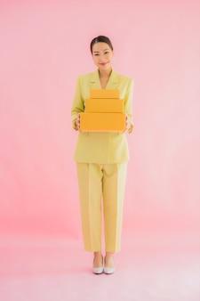 Retrato linda jovem asiática com caixa de pacote na cor