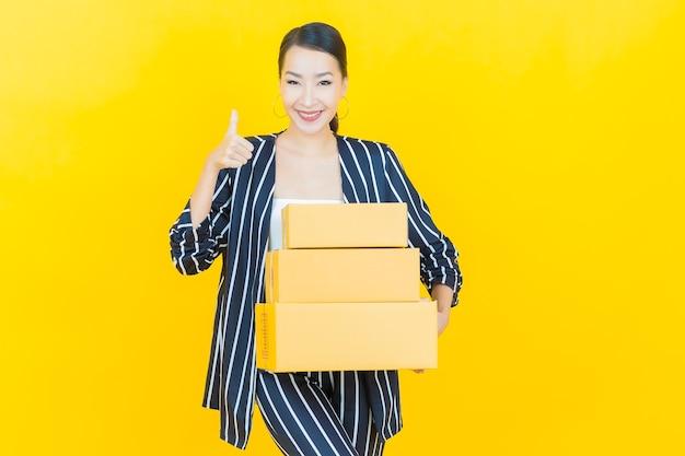 Retrato linda jovem asiática com caixa pronta para envio na cor de fundo.