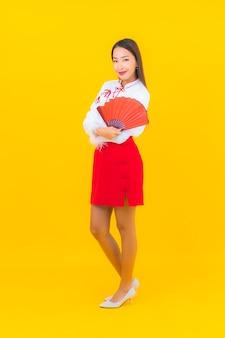 Retrato linda jovem asiática com carta de envelopes vermelhos em amarelo.