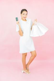 Retrato linda jovem asiática com cartão de crédito e sacola de compras na parede cor de rosa