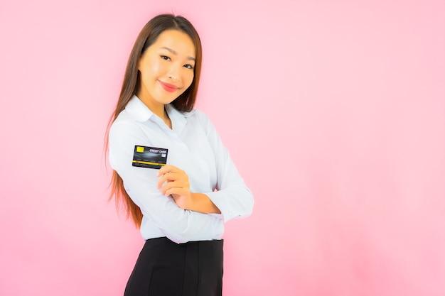 Retrato linda jovem asiática com cartão de crédito na parede rosa