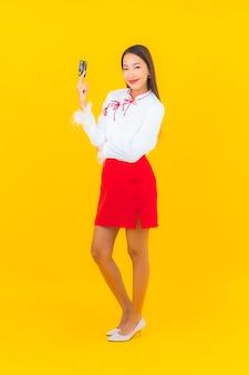 Retrato linda jovem asiática com cartão de crédito para compras online em amarelo