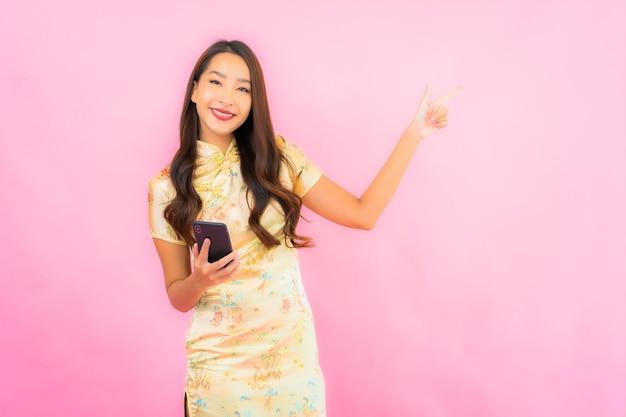 Retrato linda jovem asiática com celular inteligente na parede cor de rosa