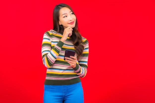 Retrato linda jovem asiática com celular inteligente na parede vermelha