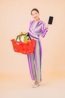 Retrato linda jovem asiática com cesta de supermercado na cor