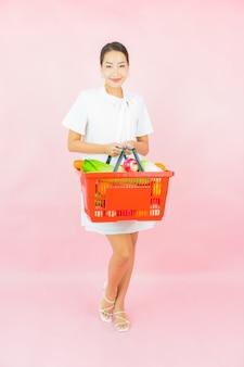 Retrato linda jovem asiática com cesta de supermercado na parede rosa
