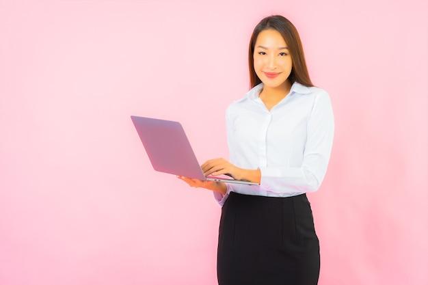 Retrato linda jovem asiática com computador laptop na parede cor de rosa