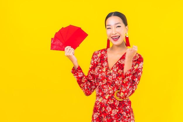 Retrato linda jovem asiática com envelopes vermelhos na parede amarela