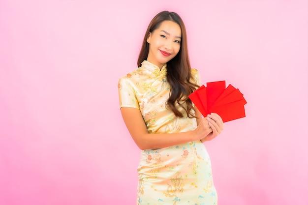 Retrato linda jovem asiática com envelopes vermelhos na parede rosa