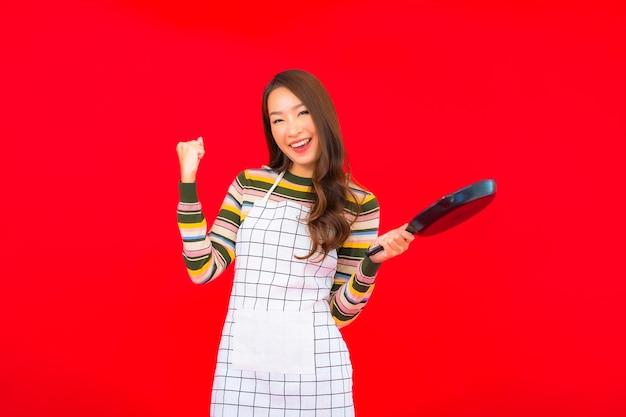 Retrato linda jovem asiática com frigideira pronta para cozinhar na parede vermelha