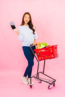 Retrato linda jovem asiática com frutas, vegetais e mercearia em uma cesta na parede rosa isolada