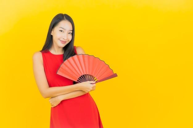Retrato linda jovem asiática com leque chinês na parede amarela