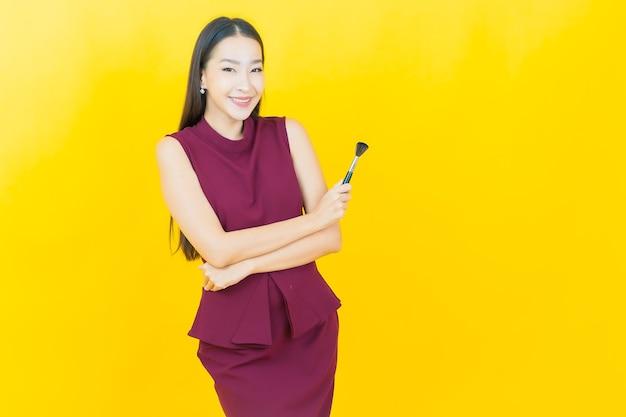 Retrato linda jovem asiática com maquiagem escova cosmética na parede amarela