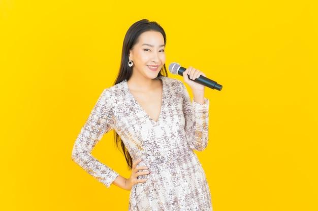 Retrato linda jovem asiática com microfone para cantar em amarelo