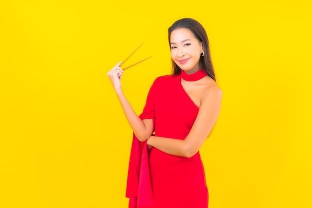 Retrato linda jovem asiática com pauzinho pronto para comer