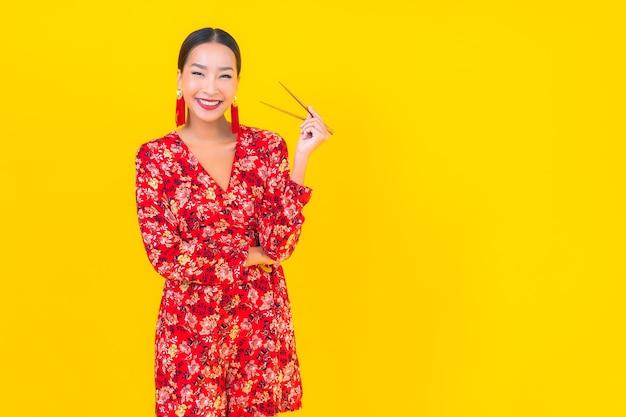 Retrato linda jovem asiática com pauzinhos na parede de cor isolada