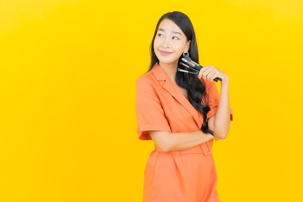 Retrato linda jovem asiática com pincel de maquiagem cosmética em amarelo