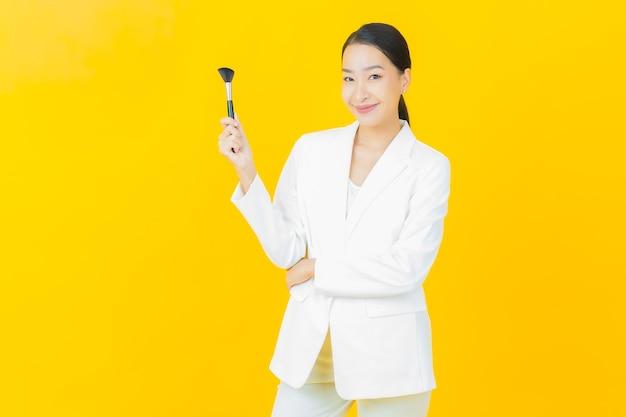Retrato linda jovem asiática com pincel de maquiagem cosmético na parede colorida
