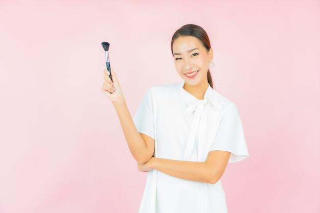 Retrato linda jovem asiática com pincel de maquiagem cosmético