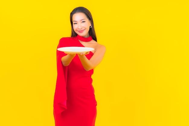Retrato linda jovem asiática com prato vazio