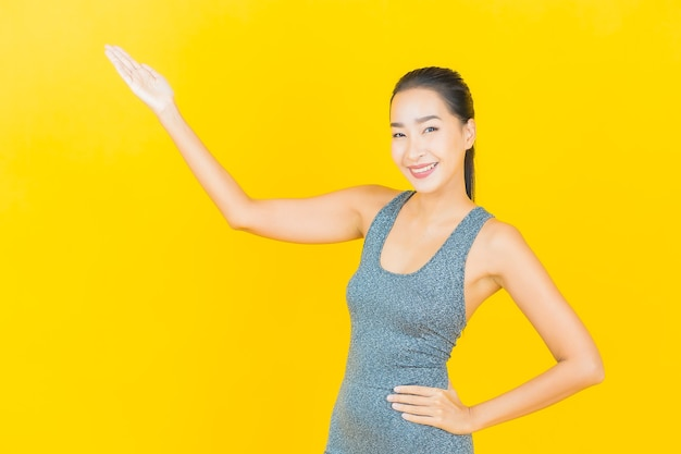 Retrato linda jovem asiática com roupa esportiva pronta para se exercitar na parede amarela.