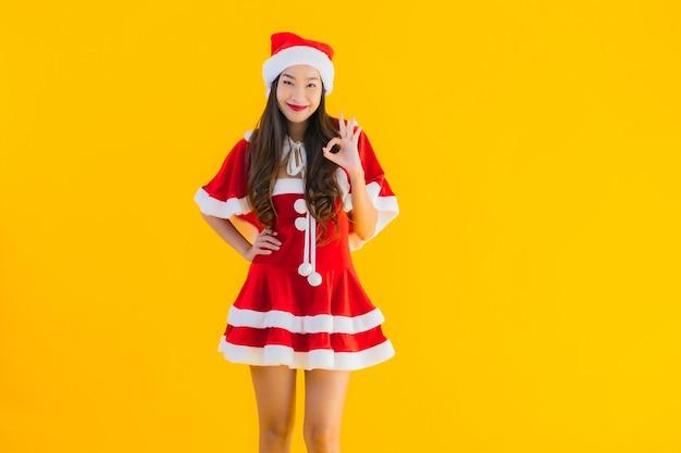 Retrato linda jovem asiática com roupas de natal e chapéu sorrindo feliz