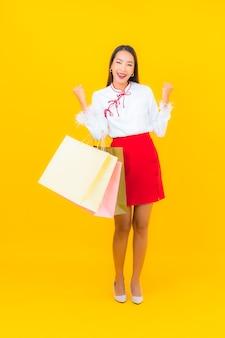 Retrato linda jovem asiática com sacola de compras e cartão de crédito em amarelo