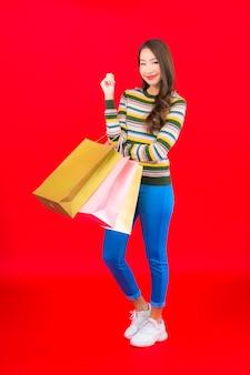 Retrato linda jovem asiática com sacolas coloridas na parede vermelha