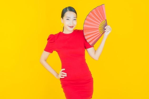 Retrato linda jovem asiática com ventilador amarelo