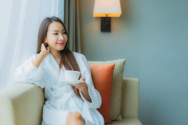 Retrato linda jovem asiática com xícara de café no sofá
