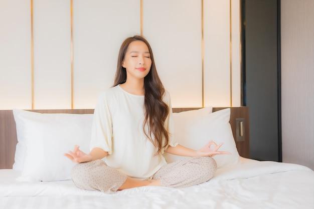 Retrato linda jovem asiática meditando na cama, no interior do quarto