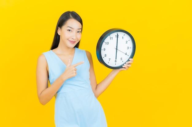 Retrato linda jovem asiática mostra alarme ou relógio na parede de cor amarela