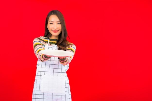Retrato linda jovem asiática mostra prato vazio na parede vermelha