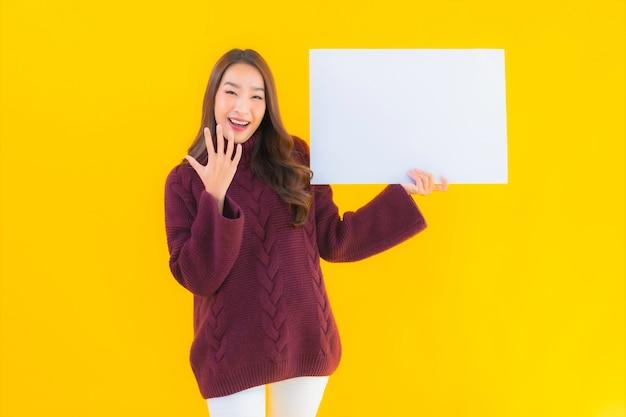 Retrato linda jovem asiática mostra um quadro de papel branco vazio