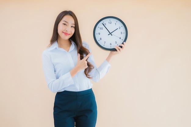 Retrato linda jovem asiática mostrar alarme ou relógio