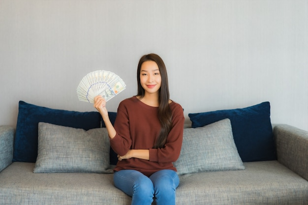 Retrato linda jovem asiática mostrar dinheiro e dinheiro no sofá no interior da sala de estar