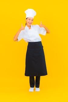 Retrato linda jovem asiática no chef ou cozinheiro uniforme com chapéu amarelo isolado.