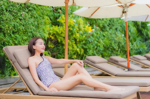 Retrato linda jovem asiática relaxando ao ar livre na piscina em viagem de férias