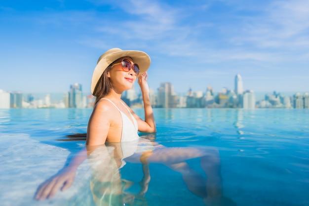 Retrato linda jovem asiática relaxando ao redor da piscina ao ar livre com vista da cidade