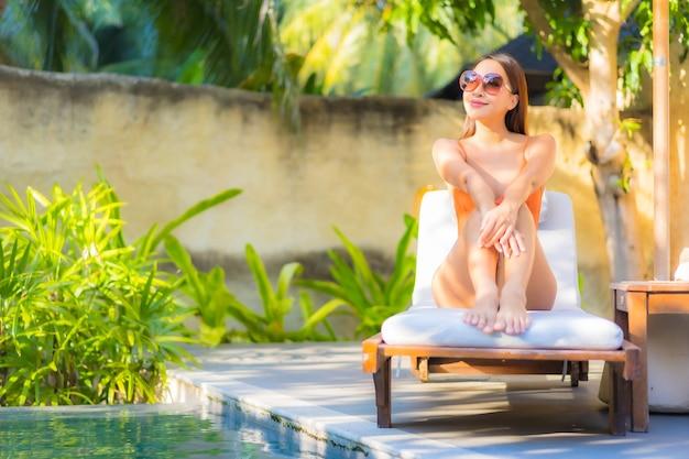 Retrato linda jovem asiática relaxando ao redor da piscina para férias de lazer
