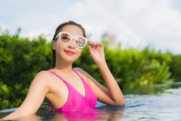 Retrato linda jovem asiática relaxando e aproveitando a piscina ao ar livre nas férias