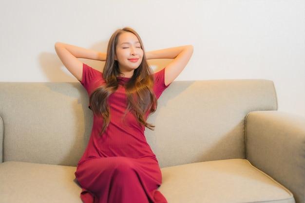 Retrato linda jovem asiática relaxando no sofá no interior da sala de estar