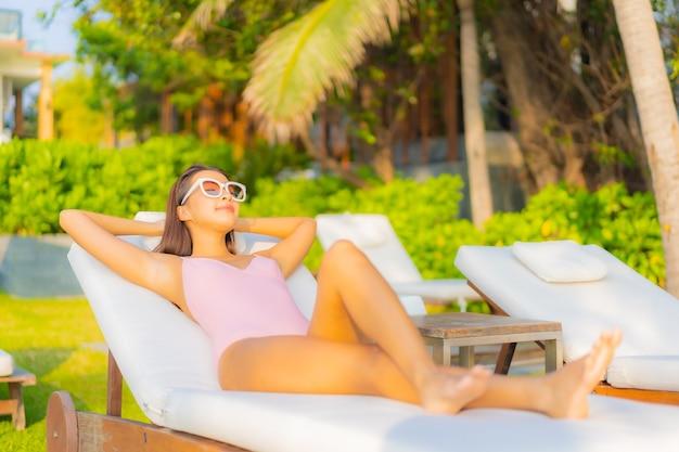 Retrato linda jovem asiática relaxando, sorrindo, aproveitando o lazer ao redor da piscina em um hotel resort